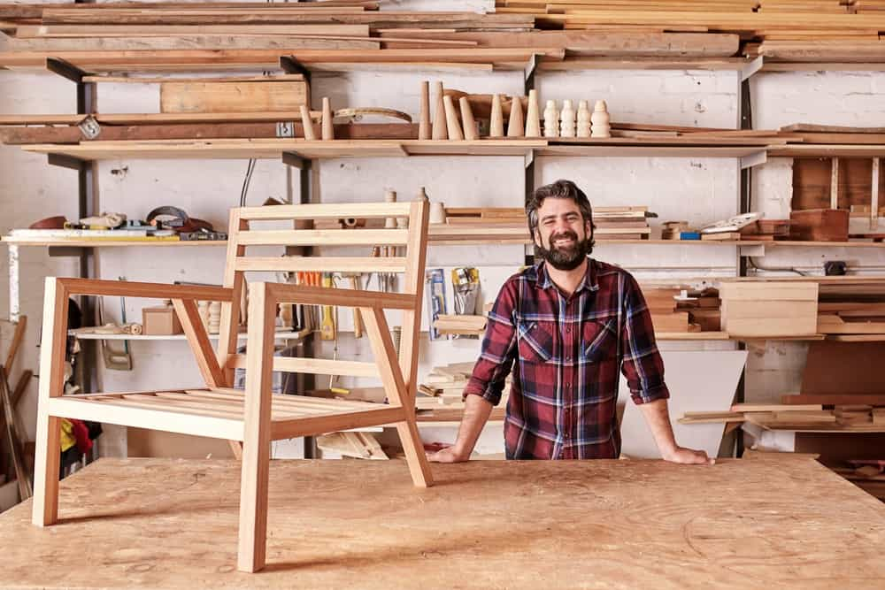 Smiling craftsman in his woodwork studio with wooden chair frame