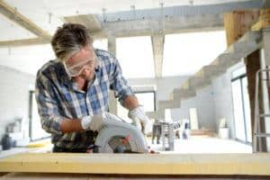 Man using electric saw inside house under construction