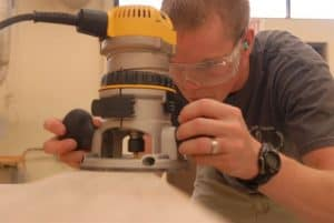 man uses a wood router in a wood working shop