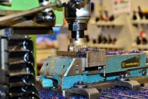 blue and gray bench vise on table, milling cutters