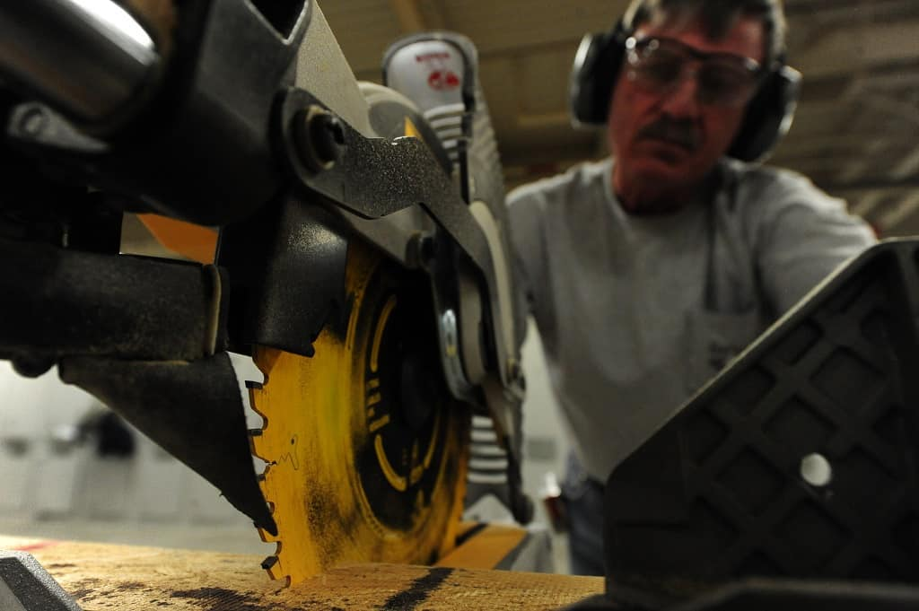 man uses a compound miter saw to cut a piece of wood