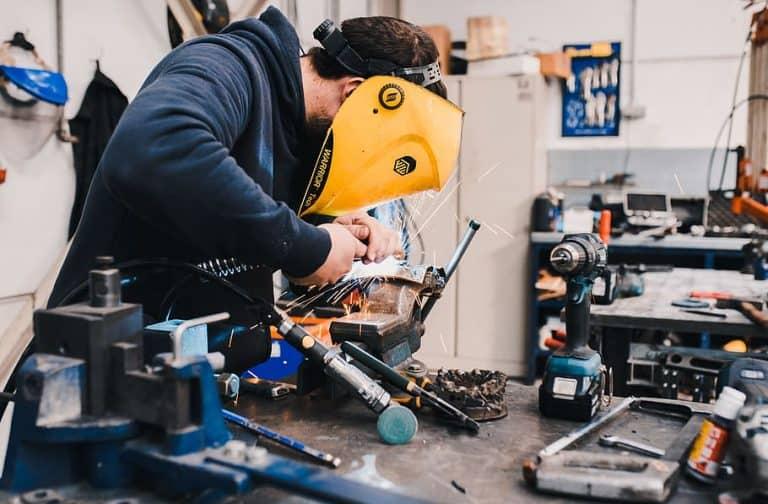 man wearing black hoodie using welding tool, work, spark, mask