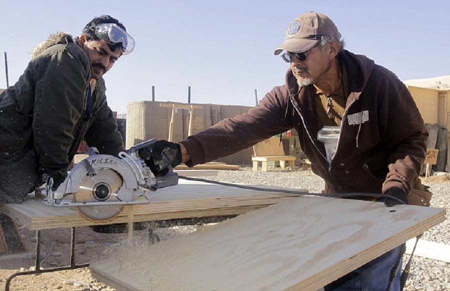 men working construction sawing wood