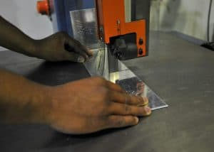 man uses a bandsaw to fabricate