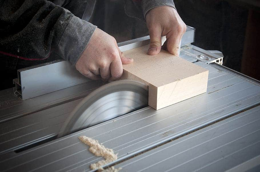 man working in a woodworking workshop uses a circular saw